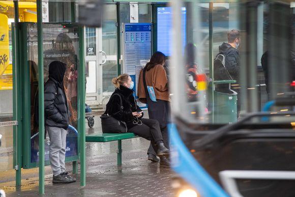 Ihmiset bussipysäkillä.
