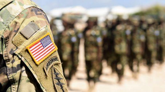 Etualalla näkyy soitlaan olkapää ja käsivarressa Yhdysvaltain lippu ja 101. maahanlaskujoukkojen tunnus. Taustalla näkyy somalialaisia sotilaita.