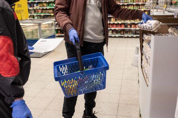 Henkilö nostaa elintarvikkeita ostoskoriinsa suojakäsineet kädessä.