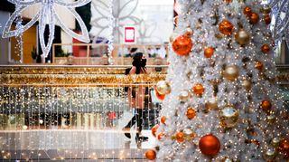 Kasvomaskiin pukeutunut nuori kävelee joulukoristeilla koristellussa ostoskeskuksessa.