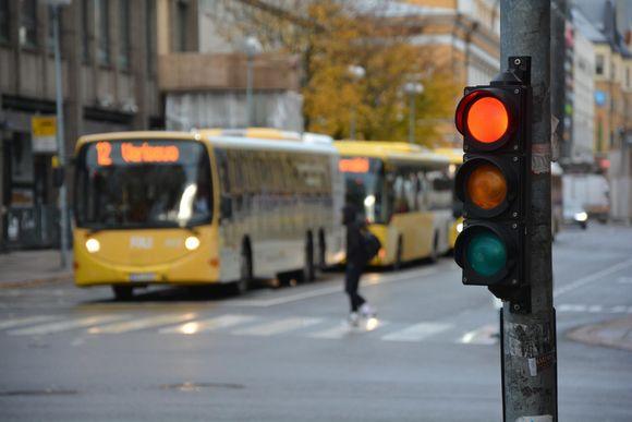 Fölibussi on pysähtynyt suojatien eteen. Kuvassa myös punainen liikennevalo.
