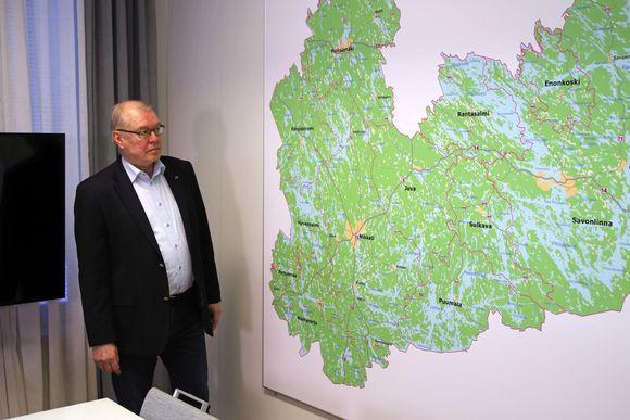 Etelä-Savon maakuntajohtaja Pentti Mäkinen työhuoneessaan. Esillä Etelä-Savon uusi kartta, jossa ei enää ole Joroista tai Heinävettä.