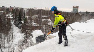 Kattotutkan työntekijä lappaa lunta pois katolta.