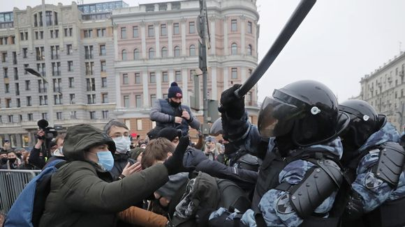 Poliisi lyö pampulla mielenosoittajaa, taustalla poliiseja ja mielenosoittajia