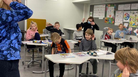 Länsiharjun koulun kolmasluokkalaiset seuraavat opettajan mallia enlannin kielen tunnilla: nyt ohjeena on laittaa pyyhekumi korvan taakse.