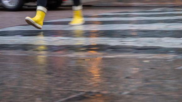 Kuvassa näkyvät sateella suojatietä ylittävät jalat, joissa on keltaiset kumisaappaat.