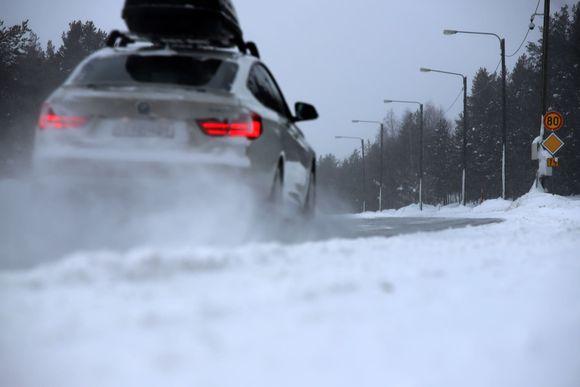 Auto ajaa talvisella tiellä, lumi pöllyää.