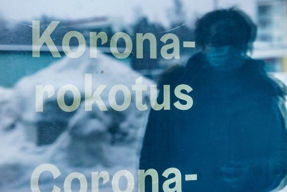 Koronarokotuspaikan lasiovesta heijastuu maskipäisen ihmisen hahmo. Ovessa lukee teksti koronarokotus.