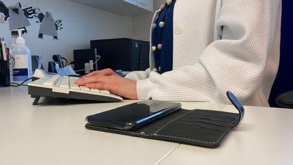 Sairaanhoitajan kädet näppäimistöllä ja ajanvarauspuhelin pöydällä
