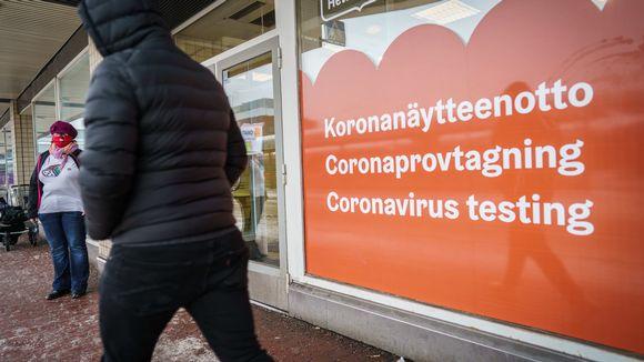 Henkilö kävelee koronatestauspaikan ohi. Ikkunassa teksti koronanäytteenotto kolmella kielellä.