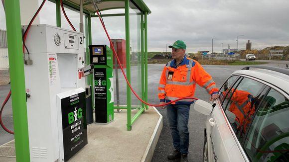 Oranssitakkinen mies tankkaa biokaasuautoaan Mustasaaren asemalla.