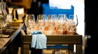Ravintolan baaritiskun takana kärryissä odottaa laseja kattauksia varten.