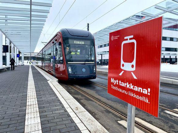 Tampereen ratikka pysähdyksissä Taysin pysäkillä Nyt tarkkana-merkin takana.