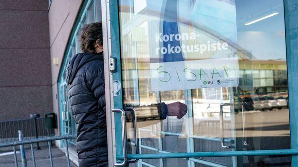 Henkilö menossa sisään koronarokotuspaikkaan. Ovessa juliste, jossa lukee koronarokotuspiste.