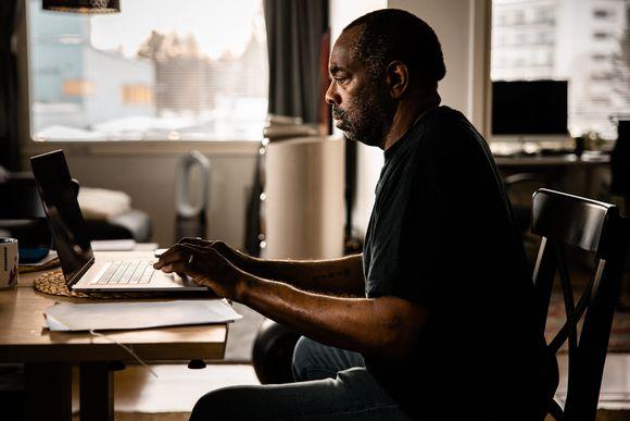 Henkilö ruokapöydän ääressä työskentelee kannettavalla tietokonella.