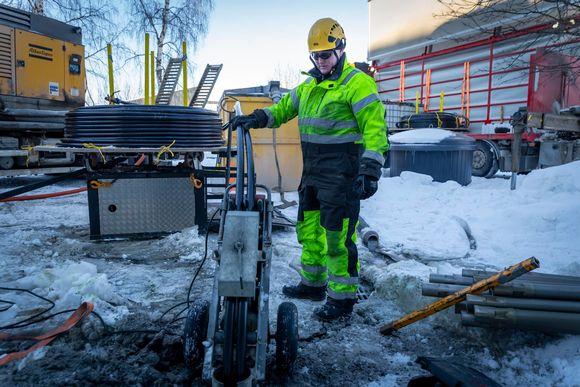 Jani Hakola asentaa lämmönkeräys putket maalämpökaivoon.