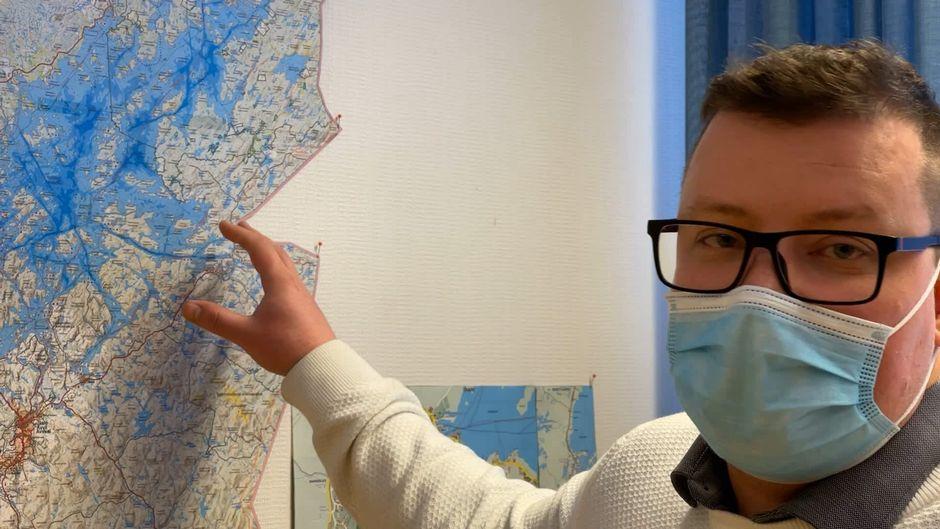 Inarin kunnanjohtaja Toni K. Laine mittailee Inarin kunnan karttaa.