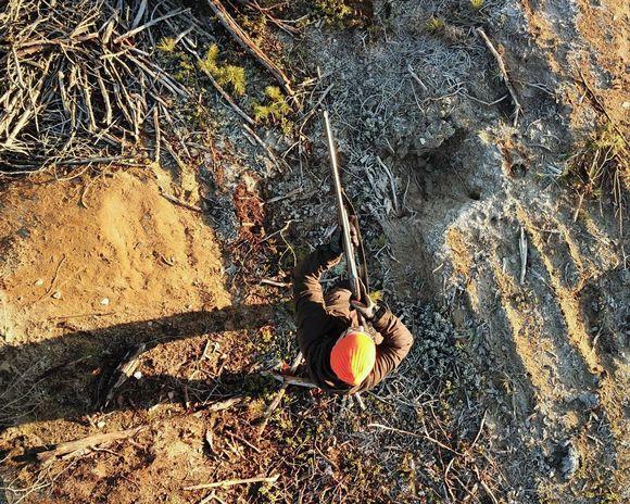 Huomioväriseen pipoon pukeutunut metsästäjä tähtää haulikolla. Kuvassa metsästäjä ylhäältä nähtynä.