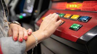 nuoren naisen käsi peliautomaatilla