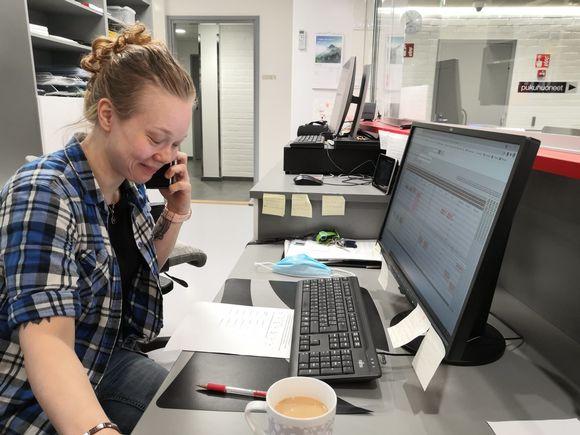 Nainen puhuu puhelimessa toimistossa.