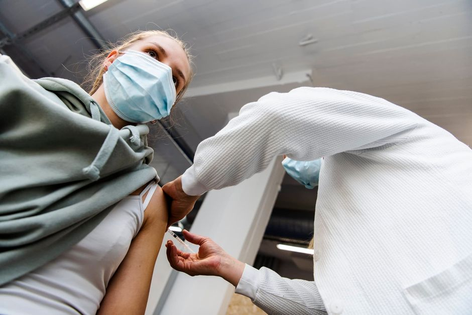 Sairaanhoitaja antoi nuorelle naiselle Pfizerin koronavirusrokotteen.