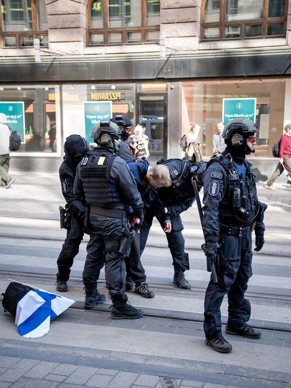 Poliisi ottaa kiinni mielenosoittajan