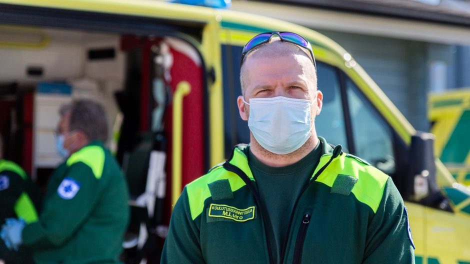 Koulutussuunnittelija Matti Luiro Lapin sairaanhoitopiiristä katsoo kameraan. Takana näkyy ambulanssi ja ensihoitaja.