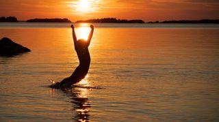 Tyttö hyppää uimaan mereen auringonlaskun aikaan.