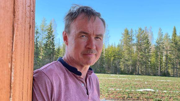 Juha Nenonen nojaa vajan seinään mansikkapellon laidassa.