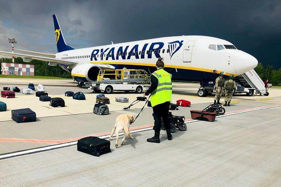 Viranomaiset tarkastivat koneessa olleiden matkatavaroita Minskin kentällä.