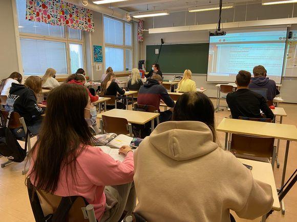 Lukiolaiset istuvat pulpeteissa oppitunnilla.