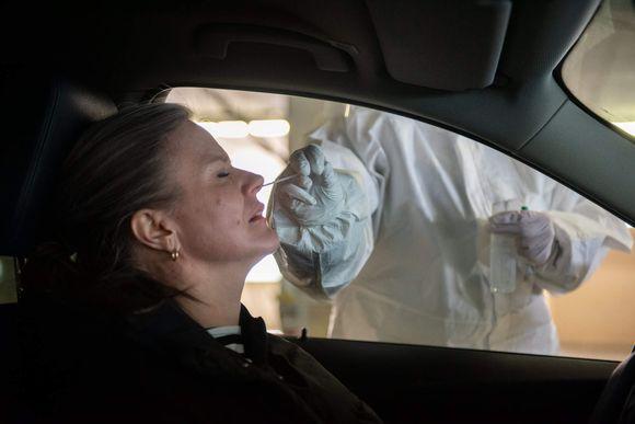 Sairaanhoitaja ottaa näytteen korona-testistä naiseltä. Korona drive-in. Messukeskus. 19.3.2021.