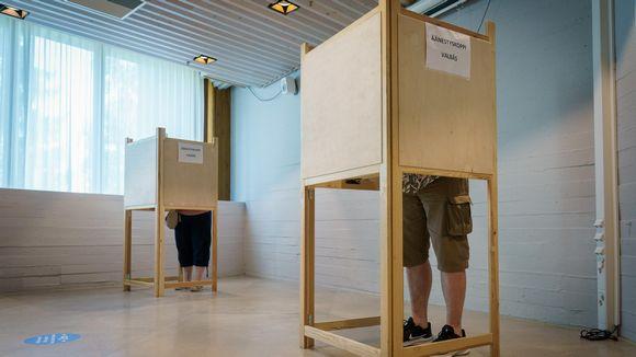 Kaksi ennakkoon äänestäjää äänestyskopeissa.