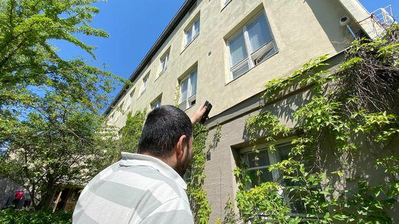 Irakilainen Hasan osoittaa huoneensa ikkunaa ulkopuolelta rakennuksen sisäpihalta, Hasan selin kuvassa.