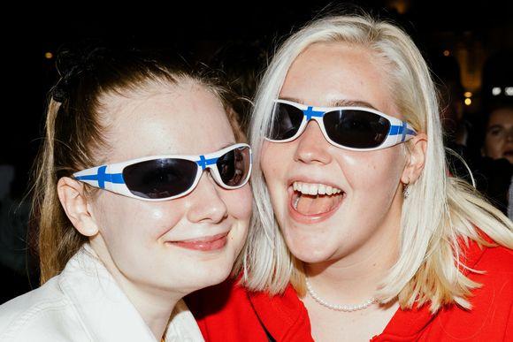 Naiset poseeraa Suomi-lasit päässä.