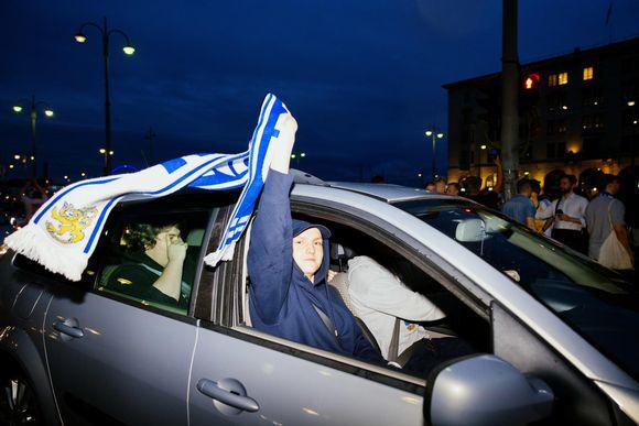 Huuhkaja fani istuu autossa ja suomen lippu liehuu.