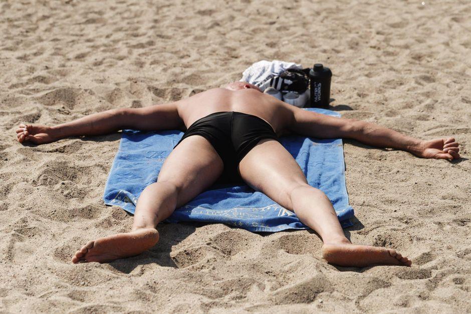 Mies ottaa aurinkoa Aurinkolahden uimarannalla Helsingissä 20. kesäkuuta 2021.