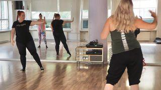 Taru Mänttäri ohjaa tanssiliikkettä, jossa käsi ja jalka ojentuvat sivulle.