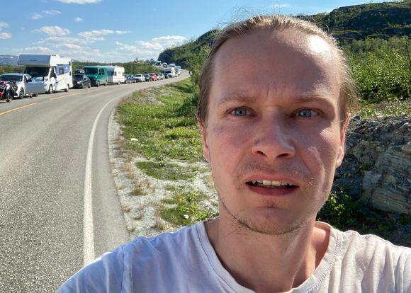 Janne Kulju katsoo kameraan Kilpisjärven rajalla, Norjan puolella. Taustalla pitkä autojono.