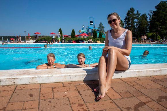 lapset Roope ja Emma vesipuiston altaassa, äiti Annastiina Rokka istuu altaan reunalla.