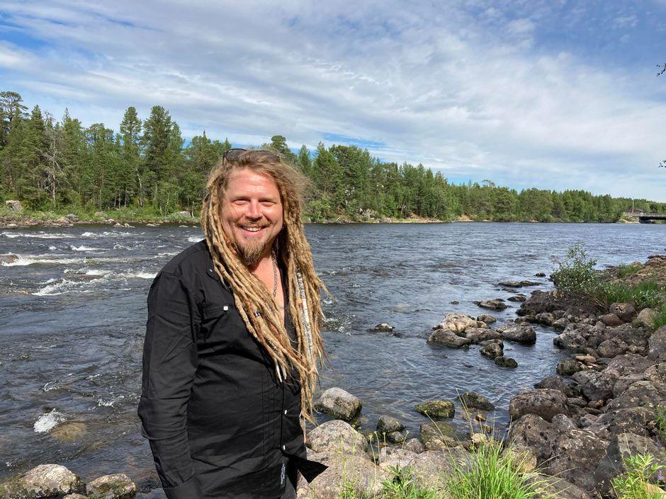 Muusikko Jonne Järvelä seisoo Juutuanjoen rannalla hymyillen.