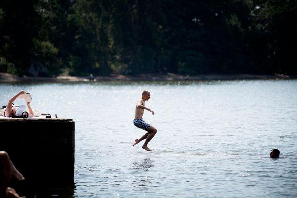 Mies hyppää laiturilta veteen.