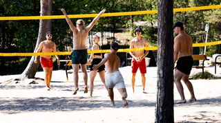 Henkilöitä pelaamassa rantalentopalloa.