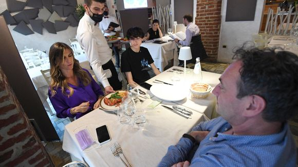 Perhe ravintolan pöydässä. Tarjoilija asettaa ruoka-annosta pöydälle.