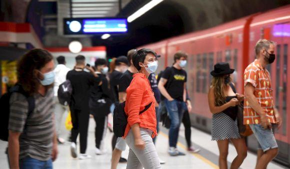Kasvomaskeihin pukeutuneita matkustajia astumassa metroon.
