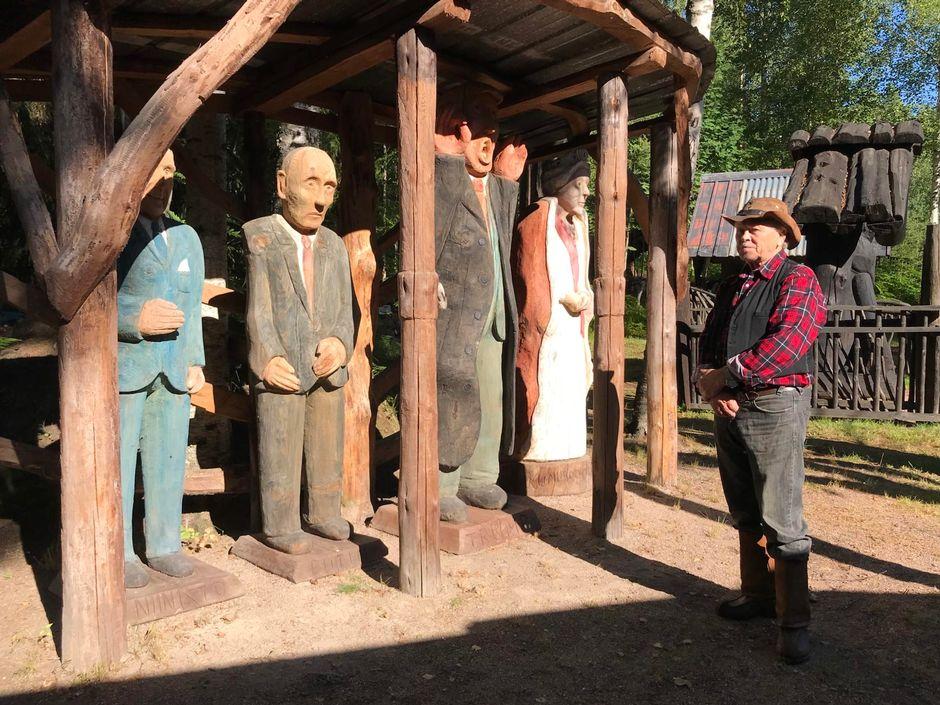 Seppo Laatunen ja hänen Niinistöä, Putinia, Trumpia ja kuningatar Elisabetia esittävät puuveistokset.