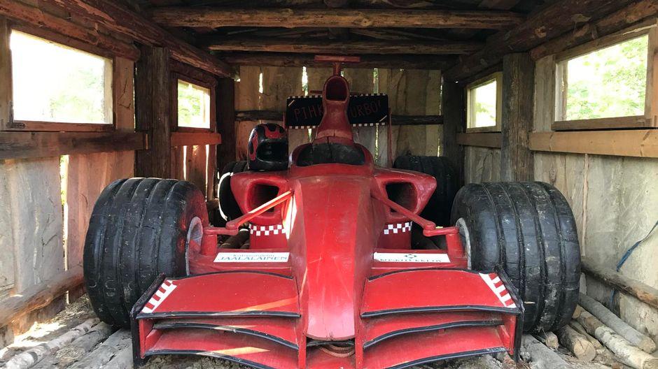 Seppo Laatusen veistämä täysikokooinen puinen punainen Formula 1 auto, kuvattu edestä päin.