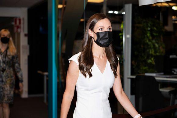 Pääministeri Marin kävelee valkoisessa mekossa käytävällä. Takana kaksi ihmistä kävelee ministerin perässä.