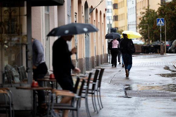 Ihmisiä kuvattuna sadesäällä Kalliossa 18.8.