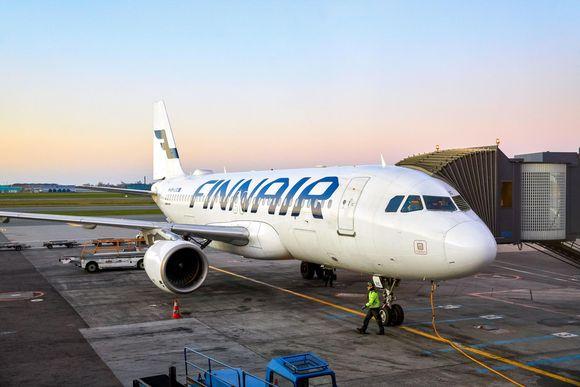 Ett Finnairflygplan parkerat på marken. I bakgrunden syns soluppgång.